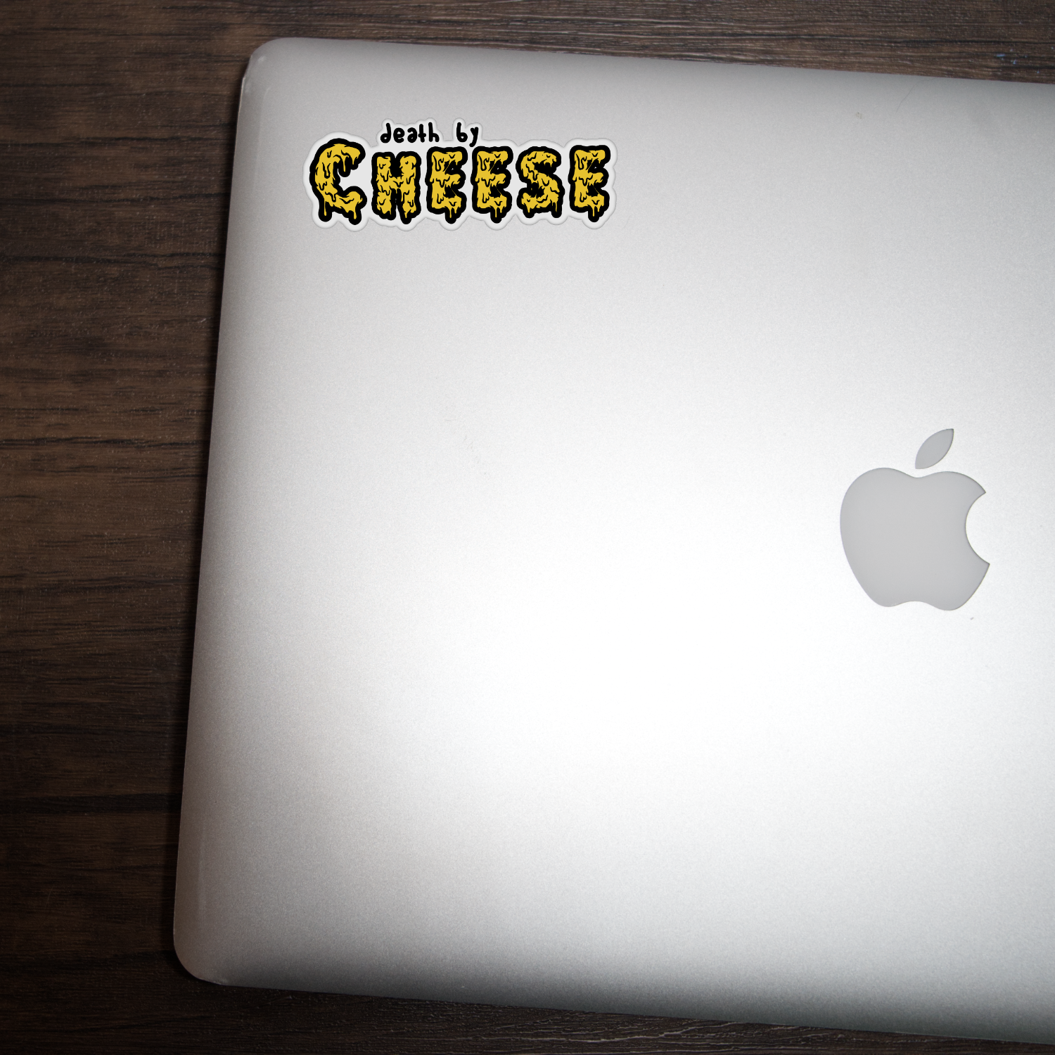 """Macbook with a vinyl sticker that says """"death by cheese"""" on it"""